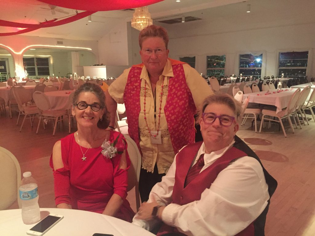 3 women at lady in red ball